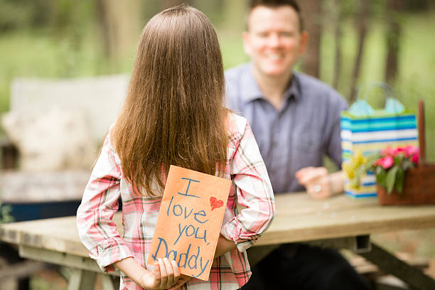 daughter gives dad handmade father's day card. outdoors. child, parent. - i love you stock photos and pictures