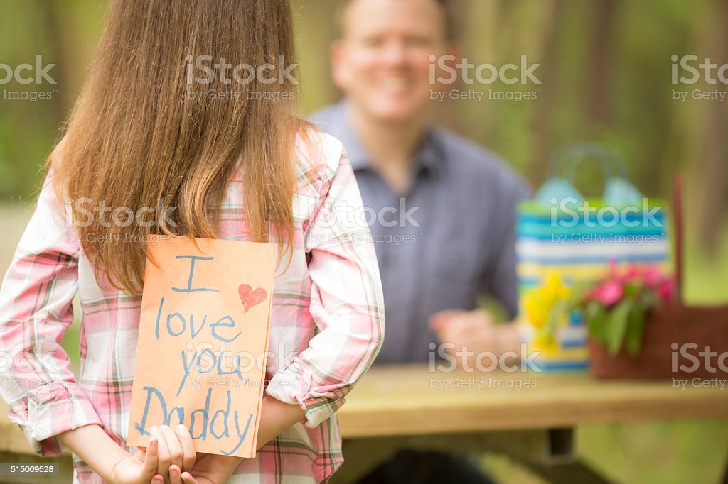 Daughter gives dad handmade Father's Day card. Outdoors. Child, parent. stock photo