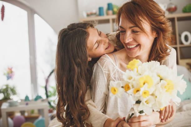 Tochter schenkt ihrer Mutter zu Hause Blumen – Foto