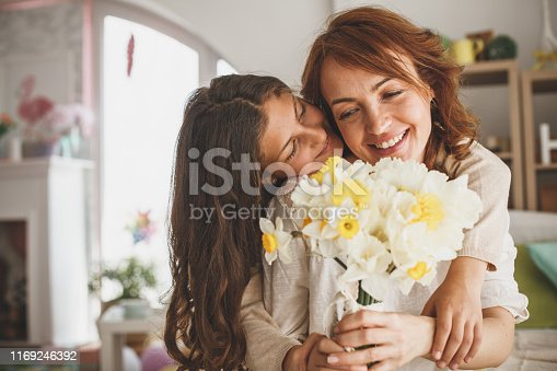 Girl is giving a bouquet of fresh daffodils to her mother at home.