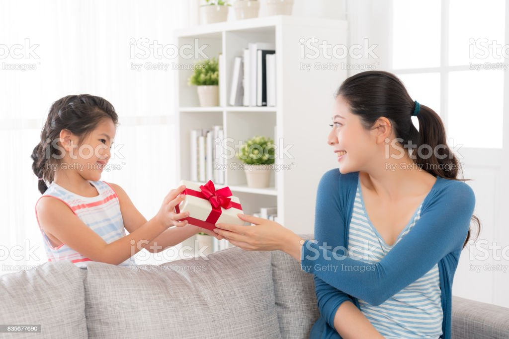daughter giving her mother a red ribbon gift box stock photo