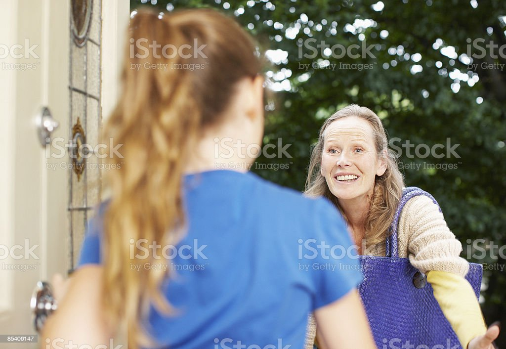 Daughter greeting mother at front door 免版稅 stock photo