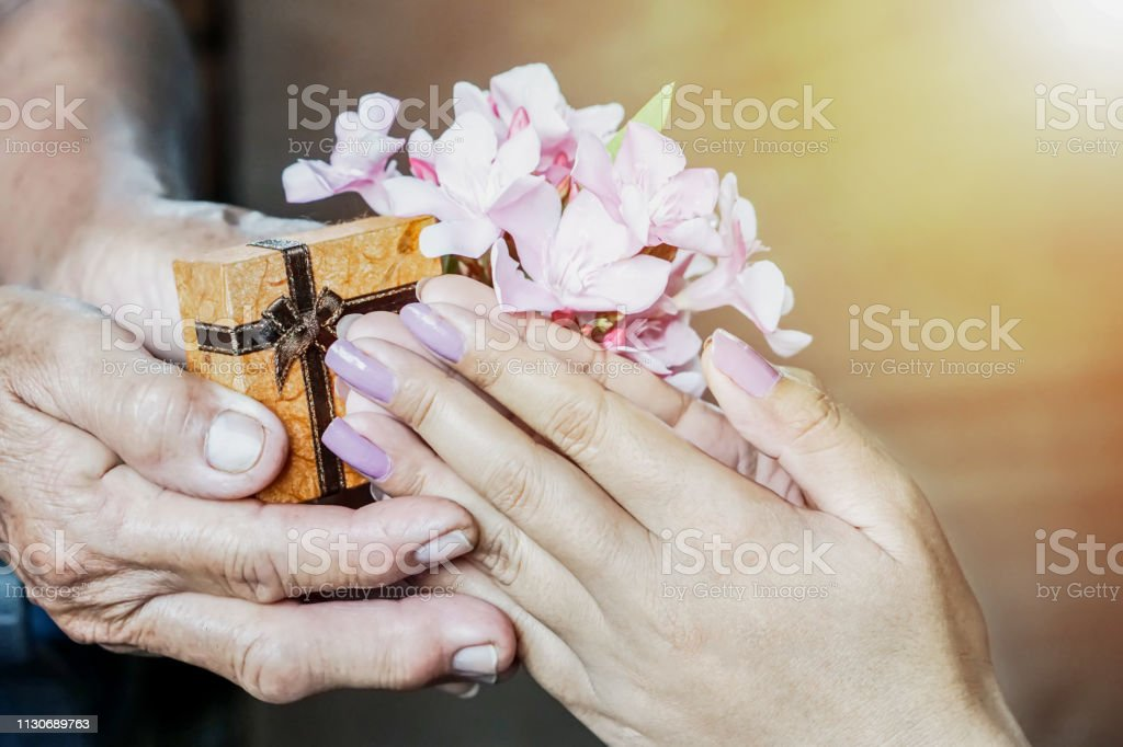 Daughter hand giving flower and present box for the mother on...