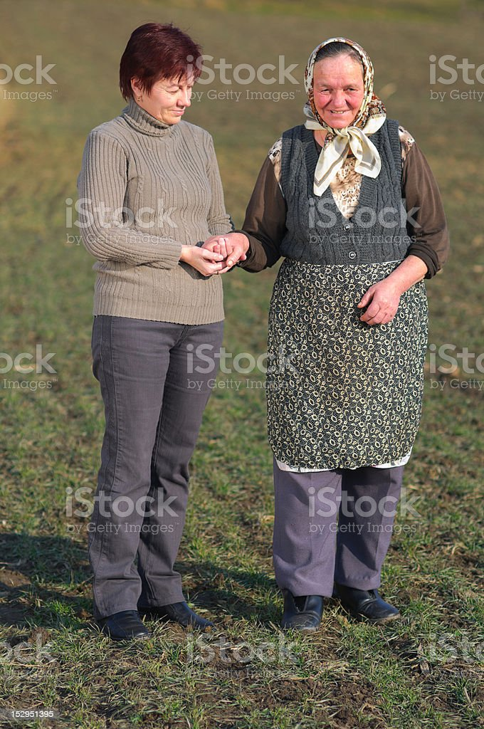 Daughter help elderly mother walk royalty-free stock photo