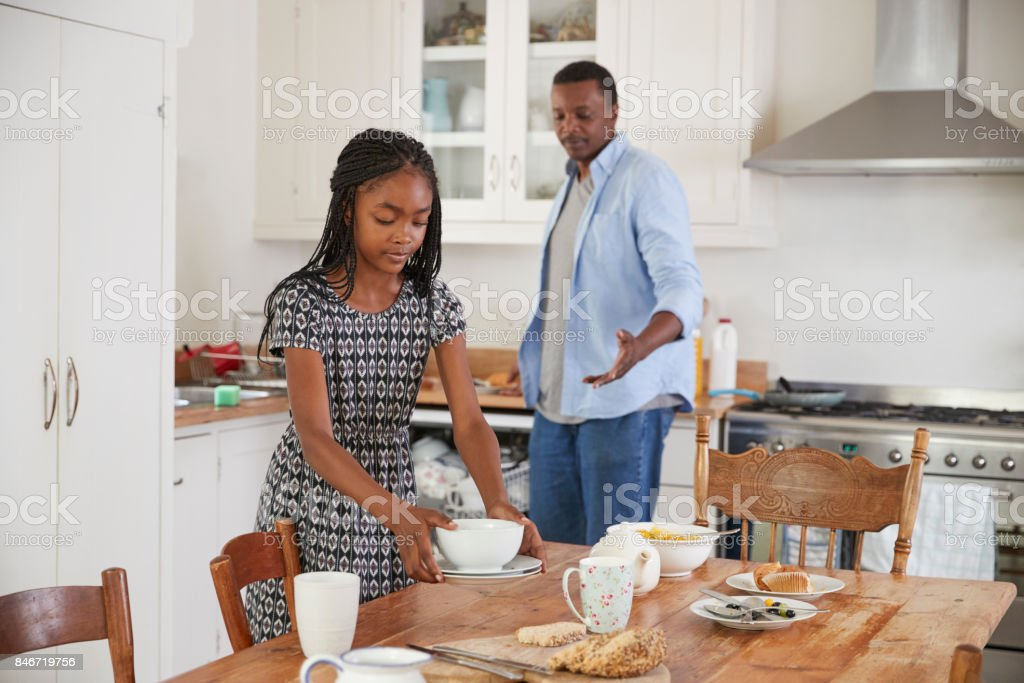 Daughter Helping Father To Clear Table After Family Meal stock photo