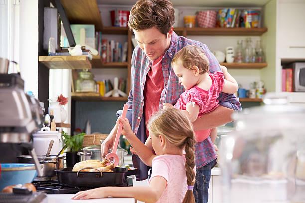 hija de padre ayudando a cook comida en la cocina - padre que se queda en casa fotografías e imágenes de stock