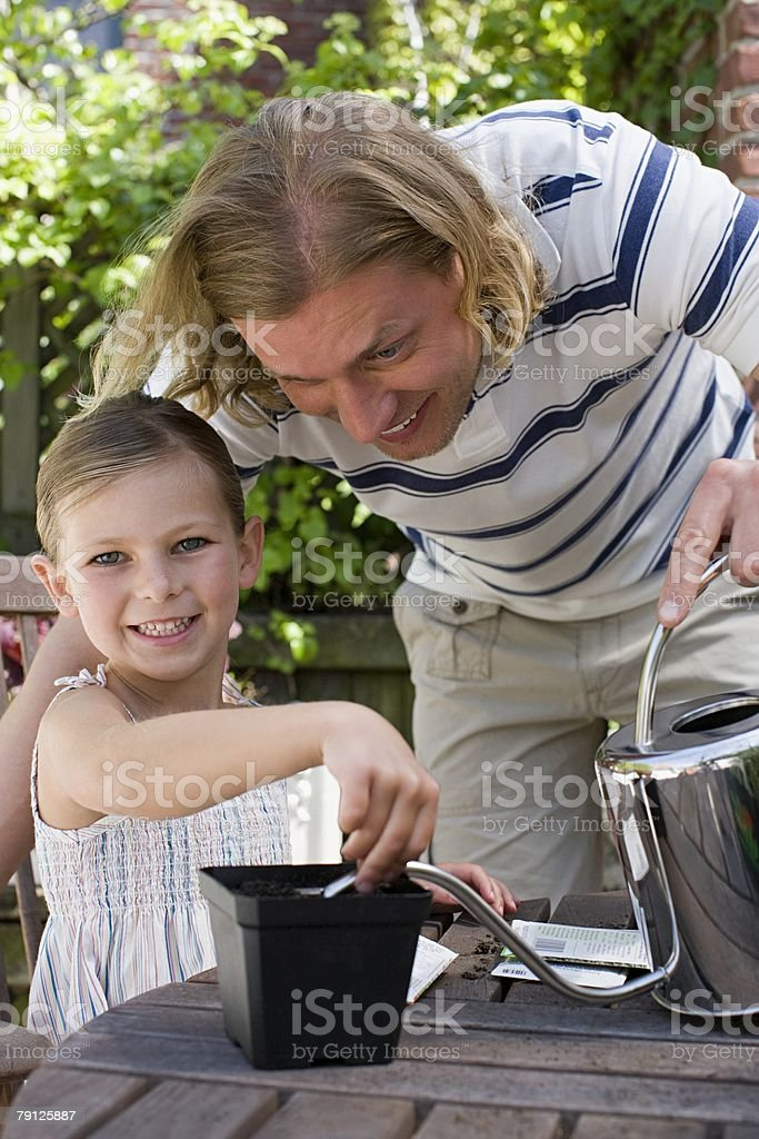 A daughter helping her father in the garden 免版稅 stock photo