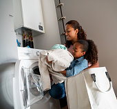 Happy daughter helping her mother with the chores at home while doing the laundry – lifestyle concepts