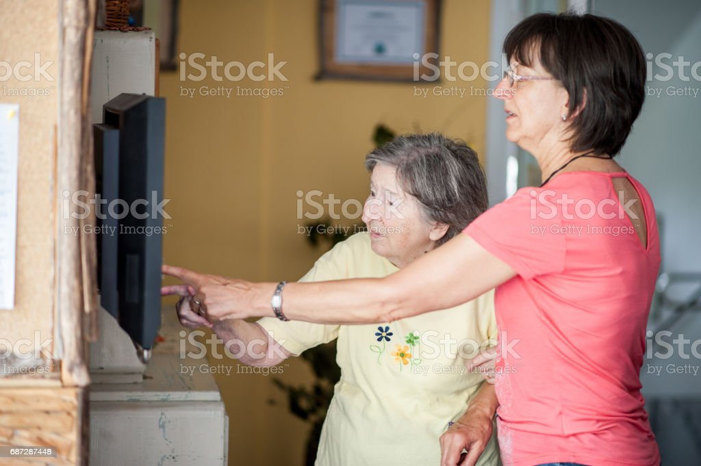 Daughter Helping Senior Mother To Find Information On Touch Screen stock photo
