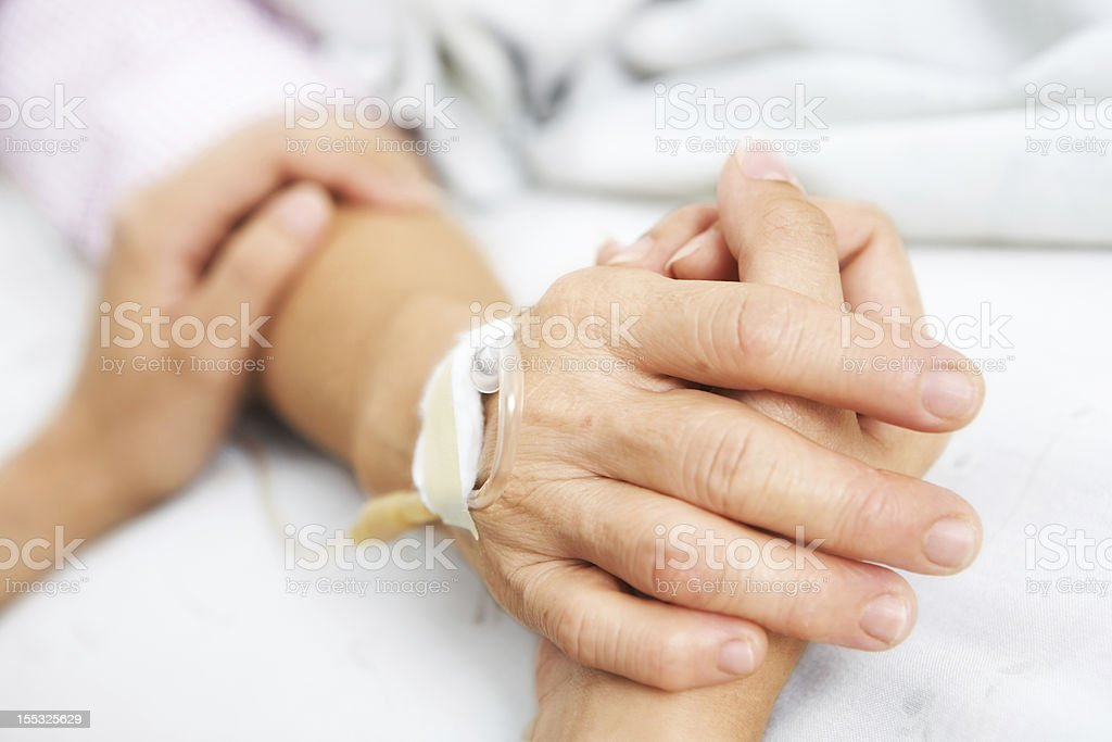 Daughter holding her mother hand in hospital stock photo