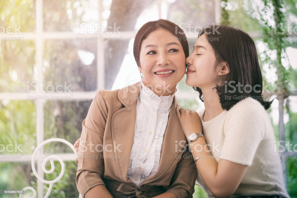 Daughter hug and kissing her mother stock photo