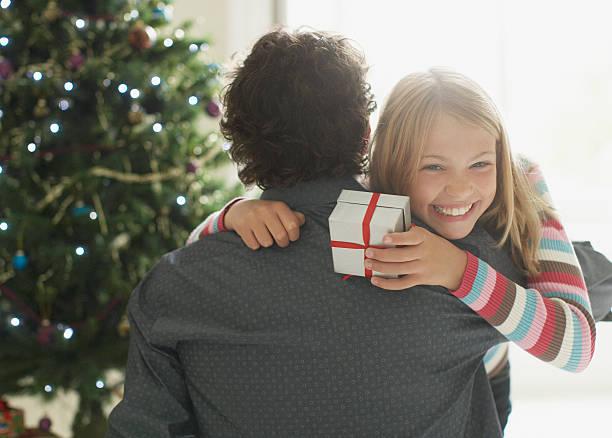 tochter umarmen vater holding christmas gift - geschenke eltern weihnachten stock-fotos und bilder
