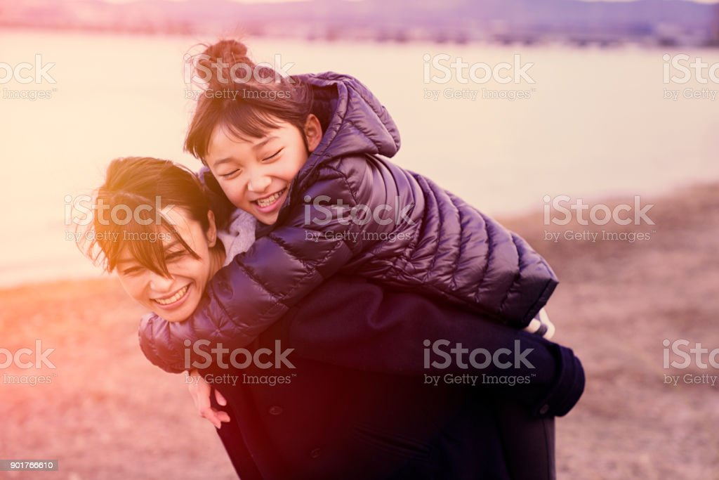 Daughter hugging mother near the lake in winter stock photo
