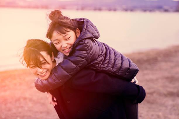 冬の湖の近くハグする母娘 - 母娘 笑顔 日本人 ストックフォトと画像