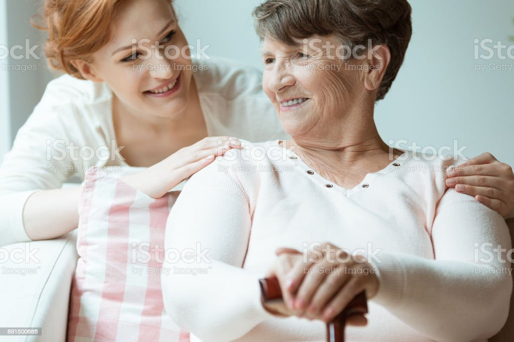 Daughter hugs smiling grandmother stock photo
