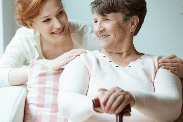 Daughter hugs smiling grandmother stock photo