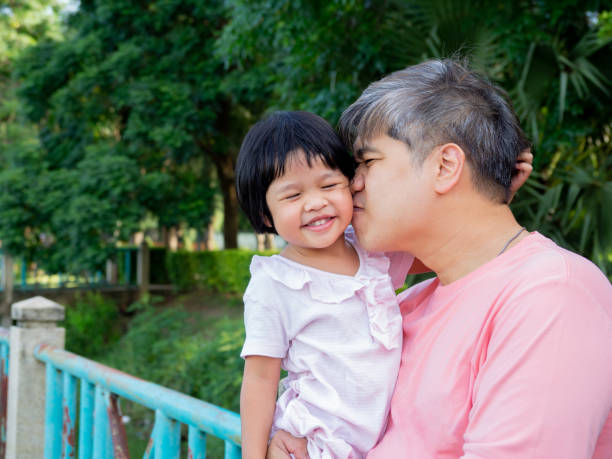 Daughter in the embrace of the father And kiss each other with love. Asia family and love concept Daughter in the embrace of the father And kiss each other with love. Asia family and love concept little girl kissing dad on cheek stock pictures, royalty-free photos & images