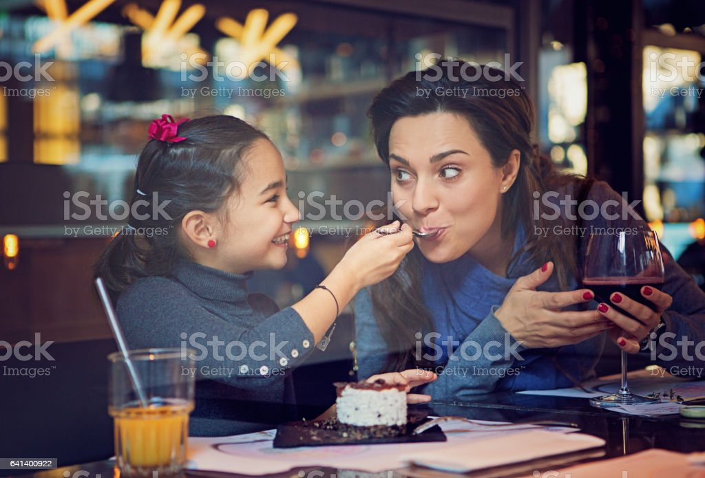 Daughter is feeding her mother with cake stock photo
