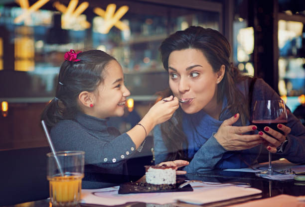 Daughter is feeding her mother with cake - foto stock