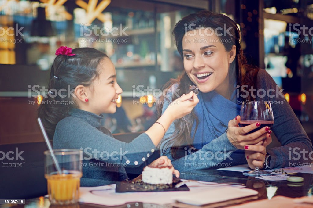 Daughter is feeding her mother with cake royalty-free stock photo