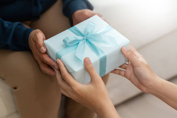 Daughter is giving a blue gift box to her mother stock photo
