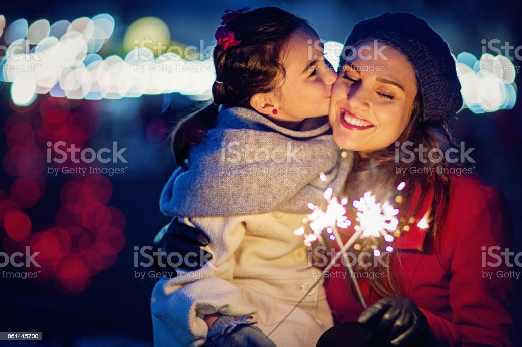 Daughter is kissing her mom at Christmas stock photo