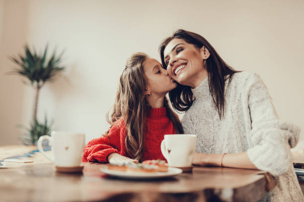 Daughter kissing her mama in cheek and smiling stock photo