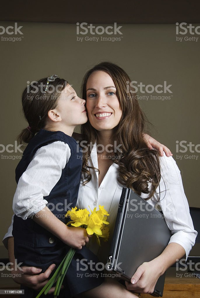 Daughter kissing her mother at the office royalty-free stock photo