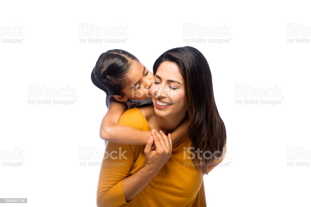 Daughter kissing her mother in the cheek stock photo