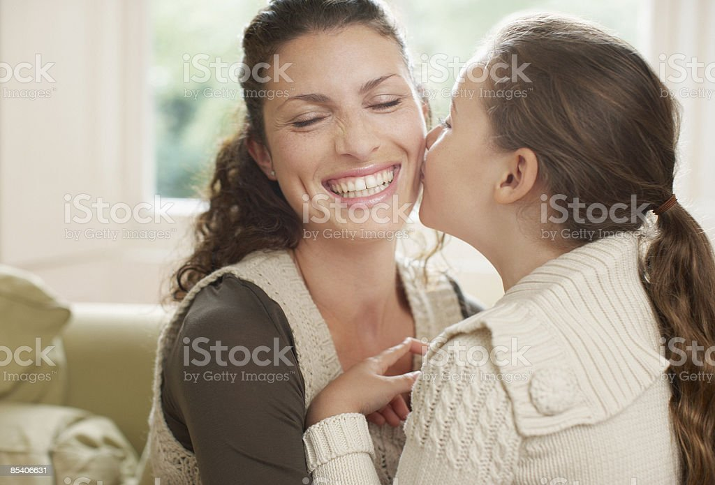 Daughter kissing mother royalty-free stock photo