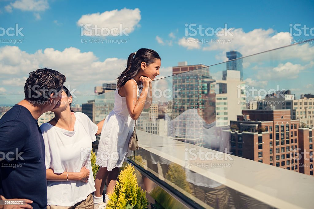 Daughter looking at New-York skyline while parents are kissing. photo libre de droits