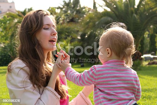 istock Daughter makes up with lipstick to the mom. Happy loving 590598326