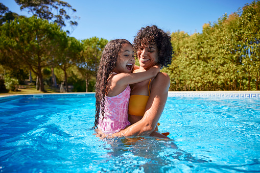 African-american daughter on mother lap inside the pool in the summer