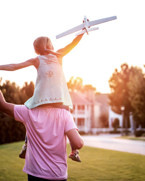 Daughter on Shoulders of Father in Park stock photo