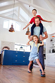 Daughter Playing Game Walking On Fathers Feet With Son On Shoulders At Home