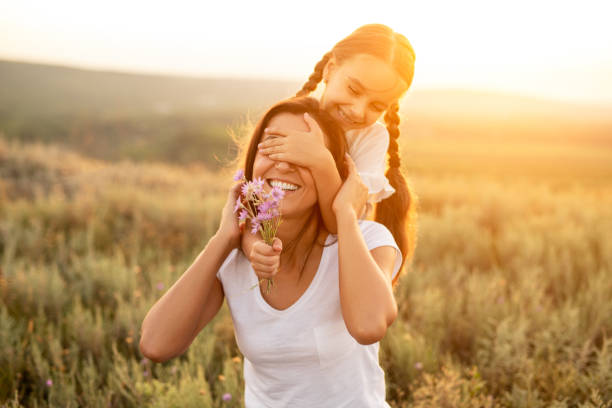 Daughter playing with mother during sunset stock photo
