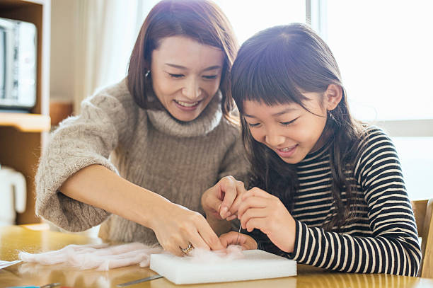 daughter playing with mother with wool felt in room - 母娘 笑顔 日本人 ストックフォトと画像