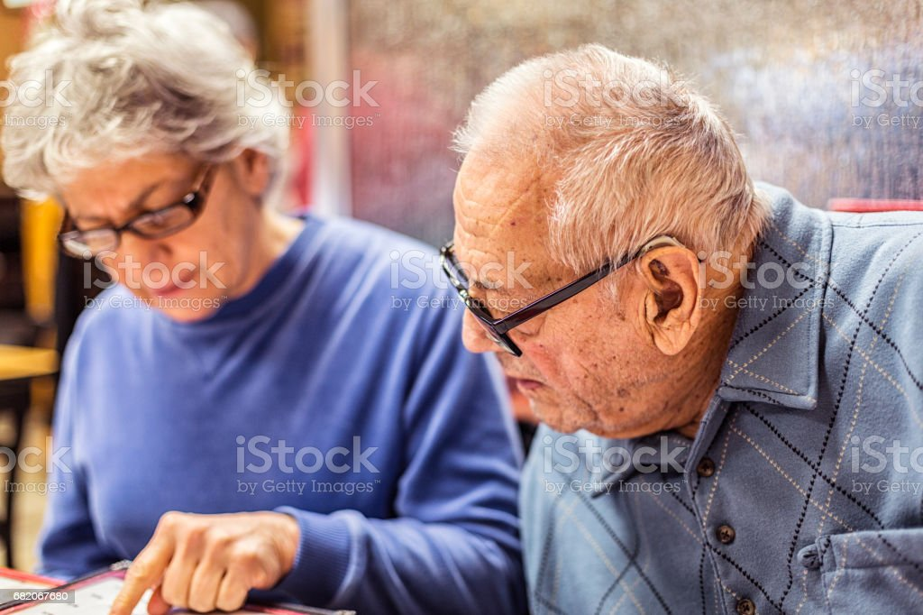 Daughter Pointing at Breakfast Menu Helping Hearing Impaired Father stock photo