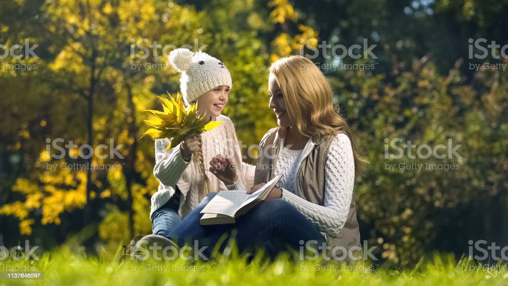 Daughter presenting mum bouquet of autumn leaves, woman reading book,...