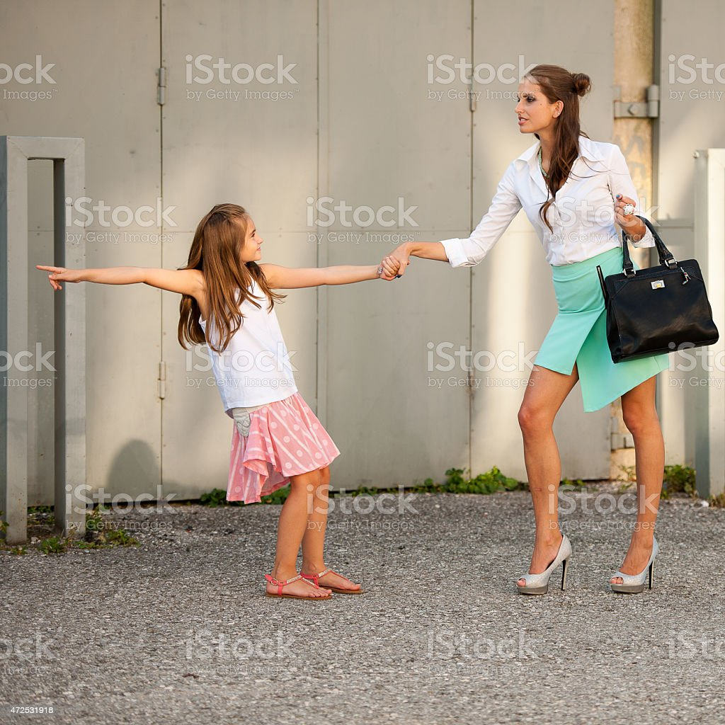 Daughter pulling mother for hand in city stock photo