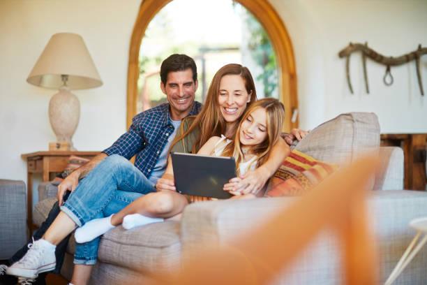 Tochter teilt ein digitales Tablet mit ihren Eltern. – Foto