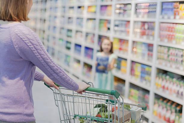 daughter showing mother box of cereal in supermarket - kinder verpackung stock-fotos und bilder