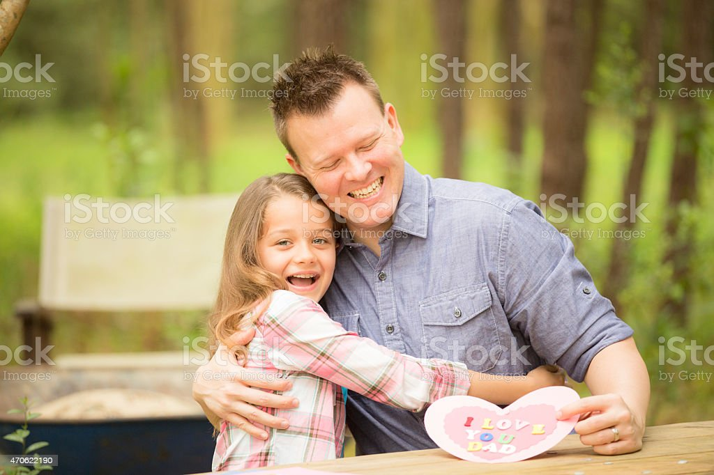 Daughter shows dad handmade Father's Day card. Outdoors. Child, parent. stock photo