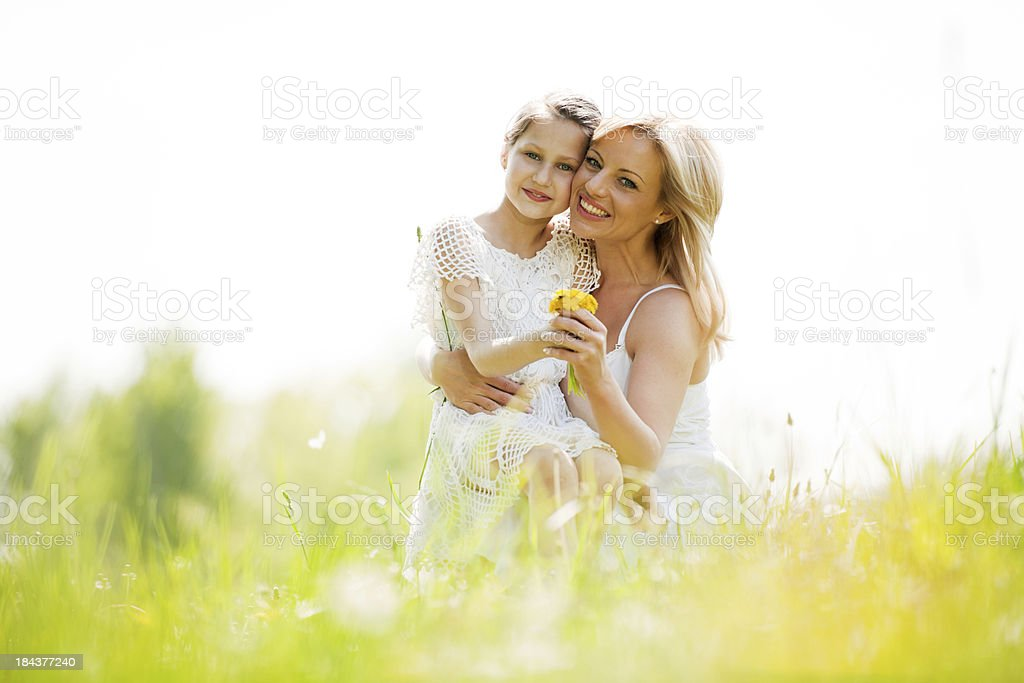 Daughter sitting in her mother's lap surrounded by nature. royalty-free stock photo
