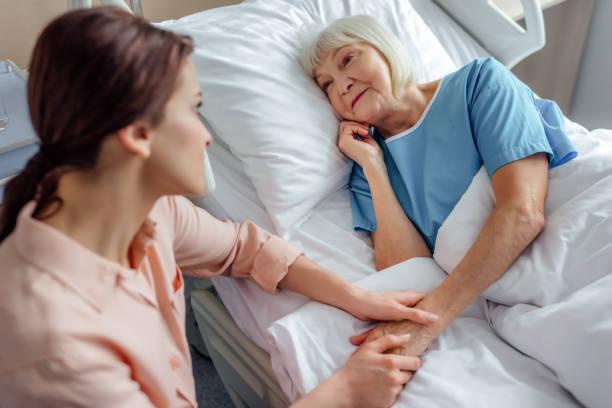 dochter zit in de buurt van senior moeder in bed en hand in hand in ziekenhuis - bezoek stockfoto's en -beelden