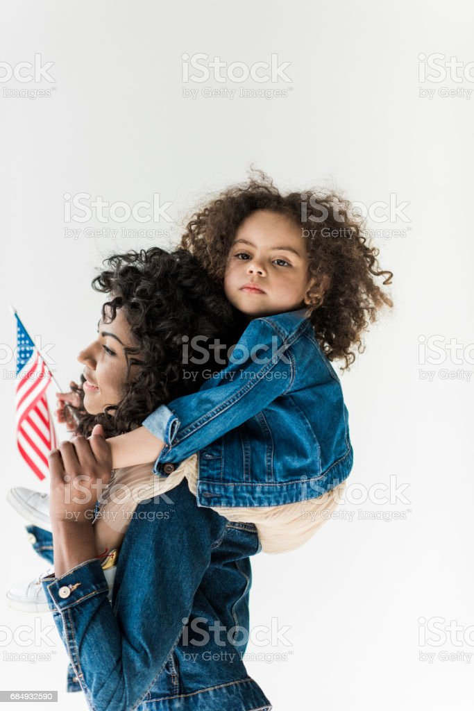 daughter sitting on shoulders of mother stock photo