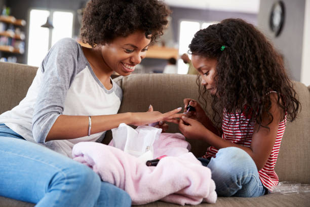 Daughter Sitting On Sofa At Home Painting Mother's Nails stock photo