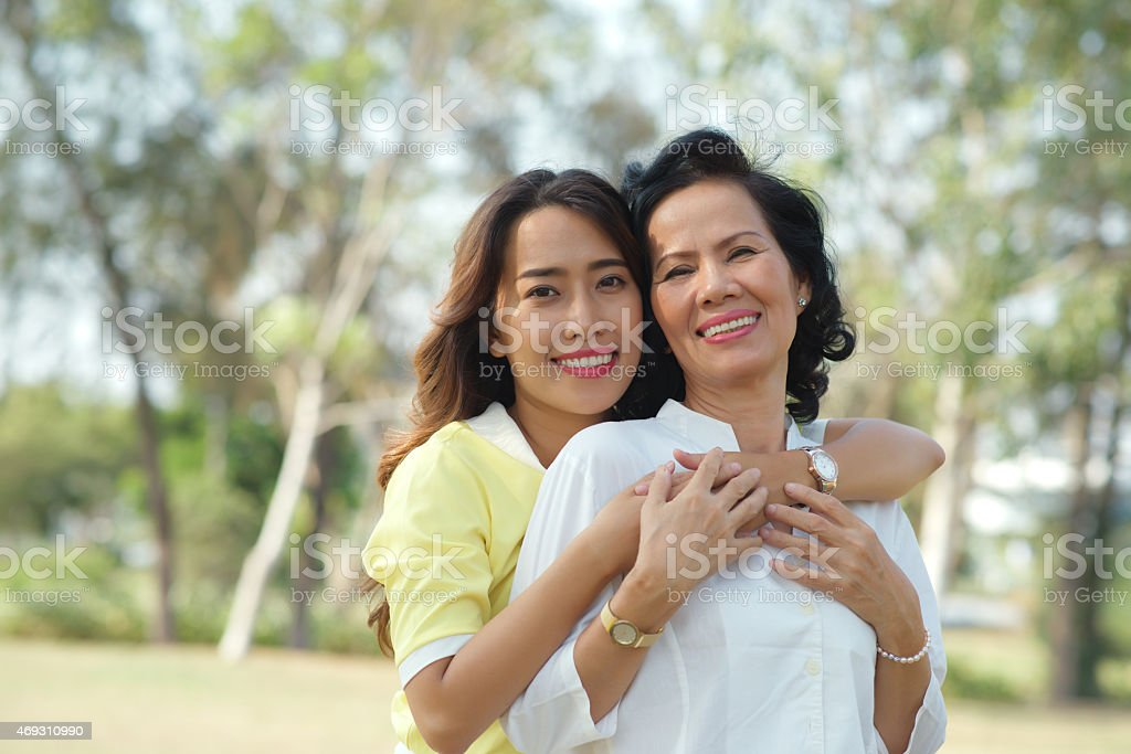 Daughter standing behind her mother with her arms around her stock photo