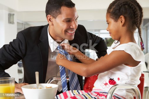 istock Daughter straightens smiling father's tie during breakfast 178988011