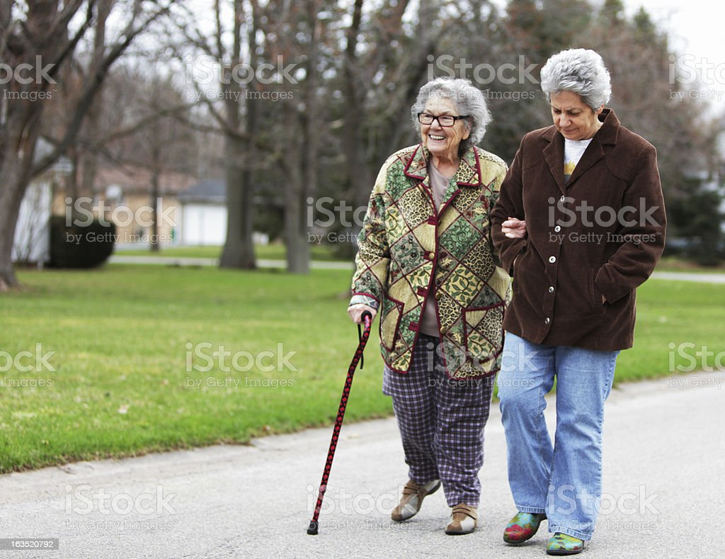 Daughter Supporting Mother Using Cane stock photo